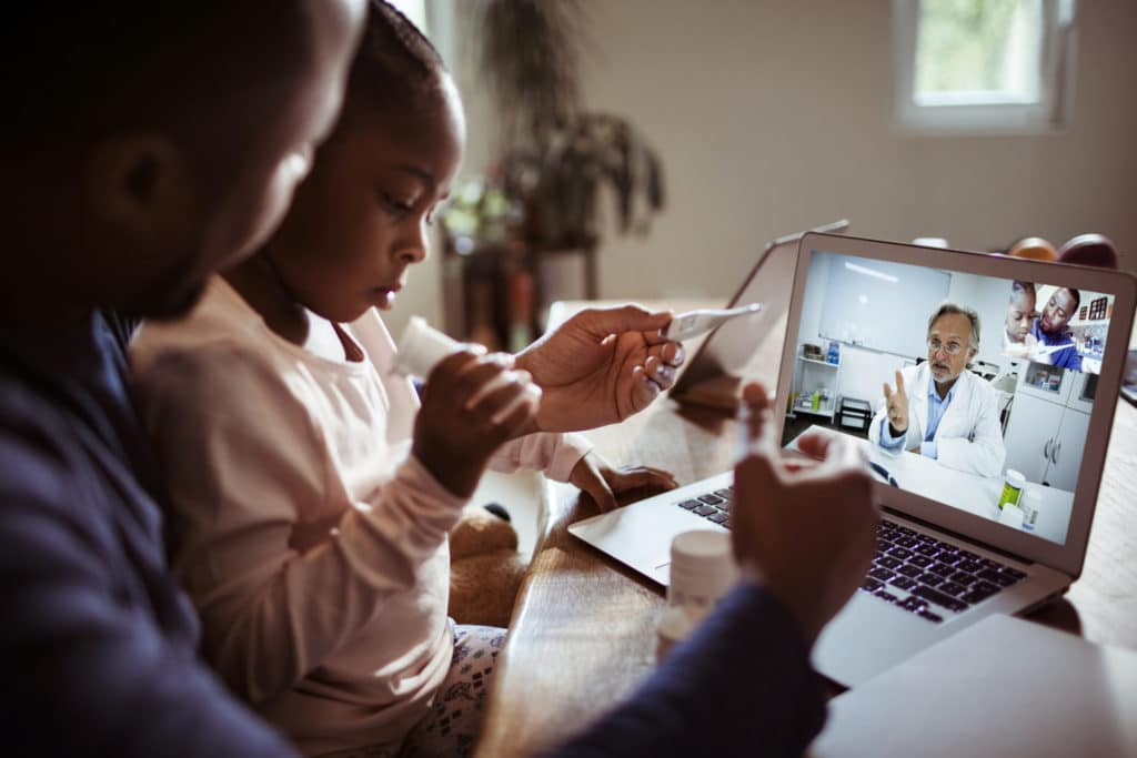 A father and daughter having a virtual telemedicine doctors appointment